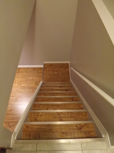 staircase leading into basement with same laminate flooring as the basement