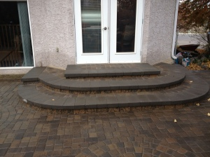 Patio landing with retaining wall blocks and cap stones and cobblestone inserts