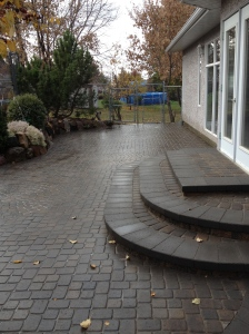 Backyard Patio in Cobblestone with circular elements and staircase with retaining wall blocks